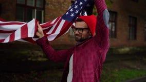 Человек развевая флаг США пока идущ вдоль улицы - концепции Дня независимости США видеоматериал