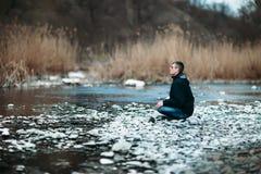 Человек размышляя в красивом ландшафте реки стоковое фото