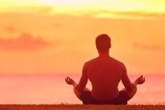 Человек размышляя в положении лотоса йоги на заходе солнца Стоковая Фотография RF