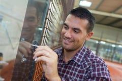 Человек раскрывает стеклянную дверь стоковое фото rf