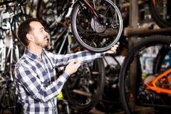 Человек рассматривает рамку велосипеда в магазине Стоковые Фотографии RF