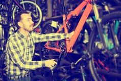 Человек рассматривает рамку велосипеда в магазине Стоковые Изображения