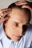 Человек рассматривая его волосы Стоковая Фотография
