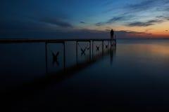 Человек рассматривая фьорд после захода солнца Стоковое Фото
