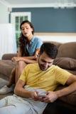Человек ревнивой женщины наблюдая используя мобильный телефон в живущей комнате Стоковое фото RF