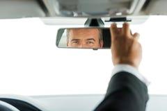 Человек регулируя зеркало автомобиля стоковое фото rf
