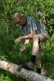 Человек режет дерево с ручной цепной пилой Стоковое Фото