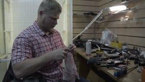 Человек ремонтируя оружия Парень с бородой очищает и ремонтирует винтовки и пистолеты armekie на его столе в студии сток-видео