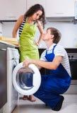 Человек ремонтируя стиральную машину и женщину стоковая фотография