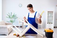 Человек ремонтируя стул в комнате стоковое фото
