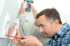 Человек ремонтируя телефон внутренной связи Стоковые Фото