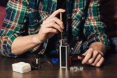 Человек ремонтируя e-испаритель Стоковое фото RF