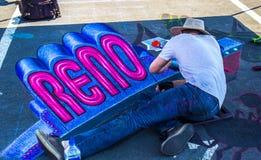 Человек рисуя знак Reno на меле прогулка Стоковая Фотография RF