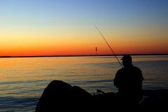 Человек рыбной ловли в заходе солнца берега озера Стоковое Изображение RF