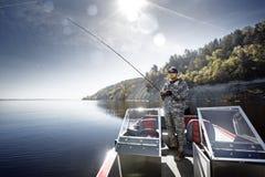 Человек рыбной ловли в шлюпке стоковые изображения rf