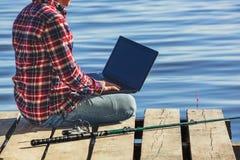 Человек рыболова работает на компьтер-книжке, сидит на деревянной пристани около озера стоковое фото rf
