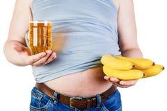 Человек сала живота Человек стоит перед выбором пива или плодоовощ Стоковое фото RF