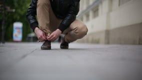 Человек связывая шнурок в улице сток-видео