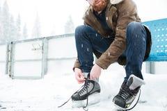 Человек связывая шнурок на коньках льда outdoors Стоковые Изображения RF