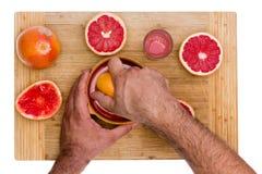 Человек сжимая рубиновые половины грейпфрута Стоковая Фотография RF
