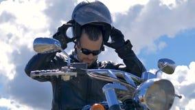 Человек сидит на его велосипеде и принимает шлем Портрет мотоциклиста видеоматериал
