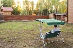 Человек сидит на качании в саде наблюдая заход солнца Стоковые Изображения