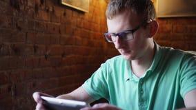 Человек сидит на маленькой таблице в кафе Человек играет пусковую площадку сидя на настольном компьютере Человек смотрит в устрой акции видеоматериалы