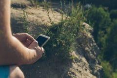 Человек сидит на том основании chating на телефоне Стоковые Изображения