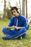 Человек сидит с таблеткой на траве Стоковые Фото