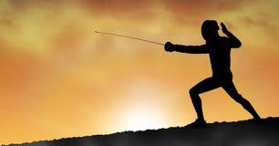Человек силуэта практикуя ограждающ спорт во время захода солнца стоковые изображения rf
