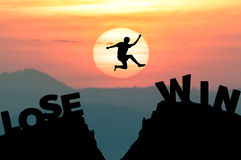 Человек силуэта скачет получает далеко от ТЕРЯЕТ для того чтобы ВЫИГРАТЬ с восходом солнца Стоковое Фото