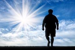 Человек силуэта толстый к идя дню Стоковое Изображение