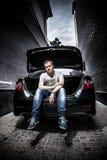 Человек сидя в багажнике автомобиля стоковая фотография