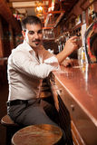 Человек сидя в баре и держа стекло Стоковое Изображение