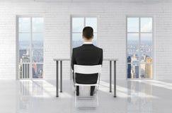 Человек сидя в комнате кирпича Стоковая Фотография