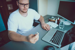 Человек сидя и смотря на пилюльках стоковое изображение