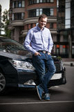 Человек сидя на клобуке автомобиля Стоковые Изображения RF