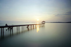 Человек сидя на мосте самостоятельно во время захода солнца Стоковое фото RF