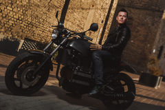 Человек сидя на мотоцикле каф-гонщика Стоковая Фотография