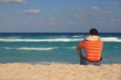 Человек сидя на песке морем Стоковые Фото
