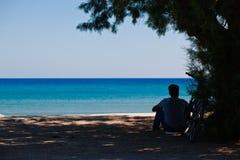 Человек сидя на песке Стоковые Фотографии RF