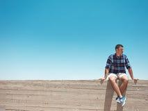 Человек сидя на стене цемента стоковое изображение