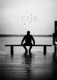 Человек сидя на стенде Стоковая Фотография