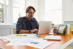 Человек сидя на столе работая на компьтер-книжке в домашнем офисе Стоковое Фото