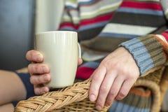 Человек сидя на стуле и держа в его кружке руки питья стоковые фото