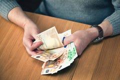 Человек сидя на таблице держа банкноты большие евро Стоковое Изображение
