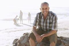 Человек сидя на утесе пока семья наслаждаясь на пляже стоковые фото