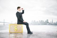 Человек сидя на чемодане с наличными деньгами Стоковое Фото