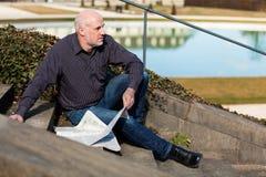 Человек сидя на шагах читая газету Стоковые Фотографии RF