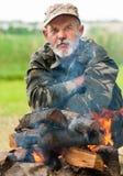 Человек сидя около костра Стоковое Фото
